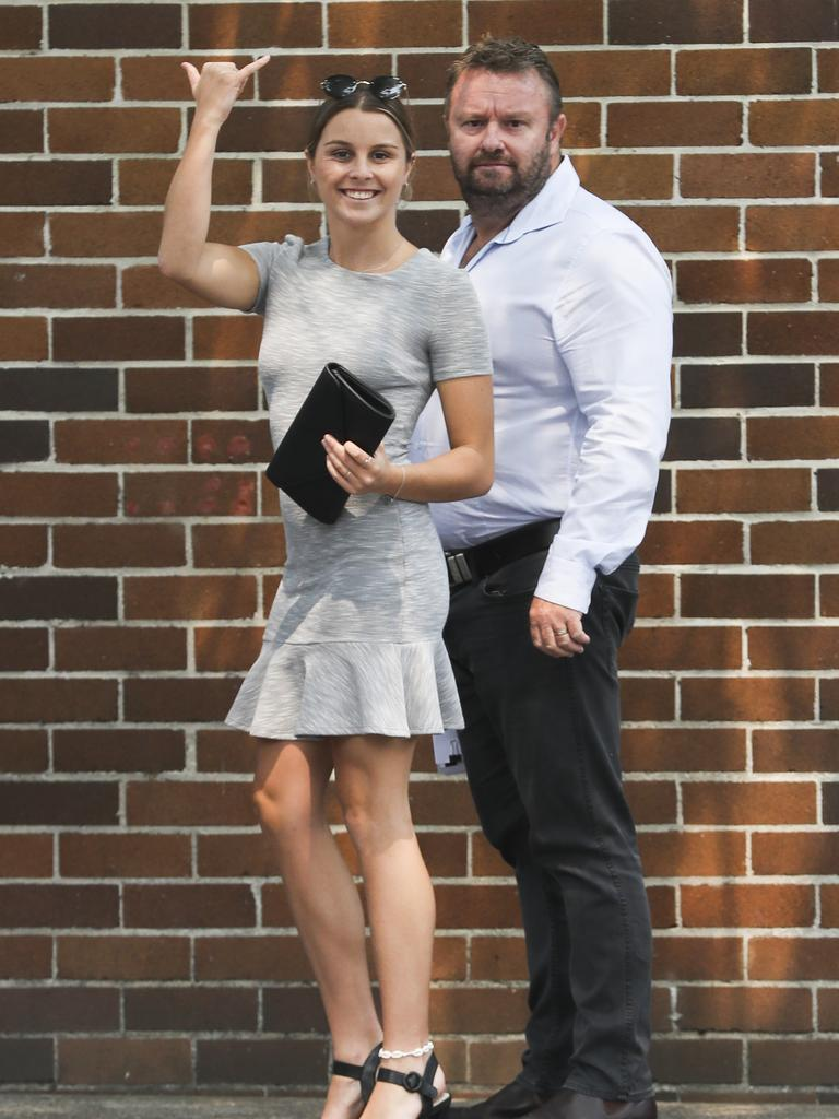 "Cameron Fisher throws a ""shaka"" outside Waverley Local Court. Picture: Dylan Robinson"