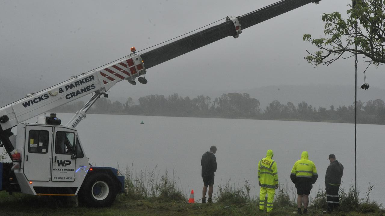 Police watch as the dive team secure the submerged vehicle along Yamba Rd just outside of Maclean on Saturday morning, January 18, 2020.