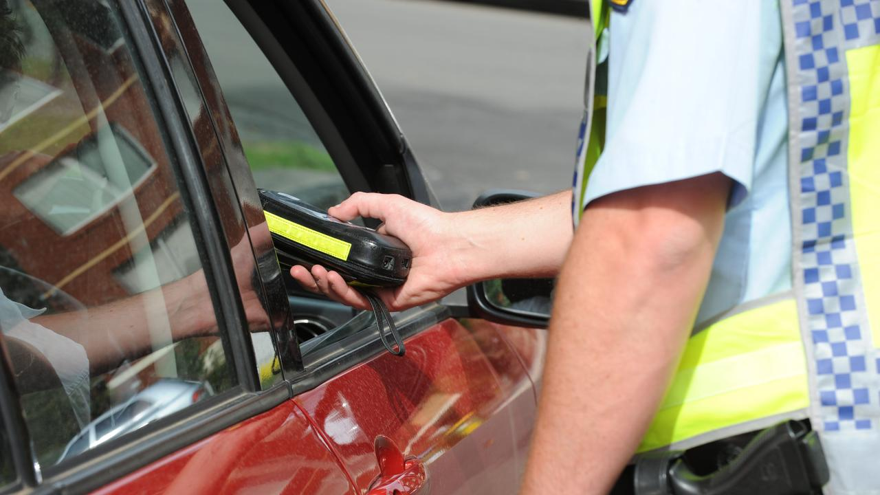 Police breath testing a person.