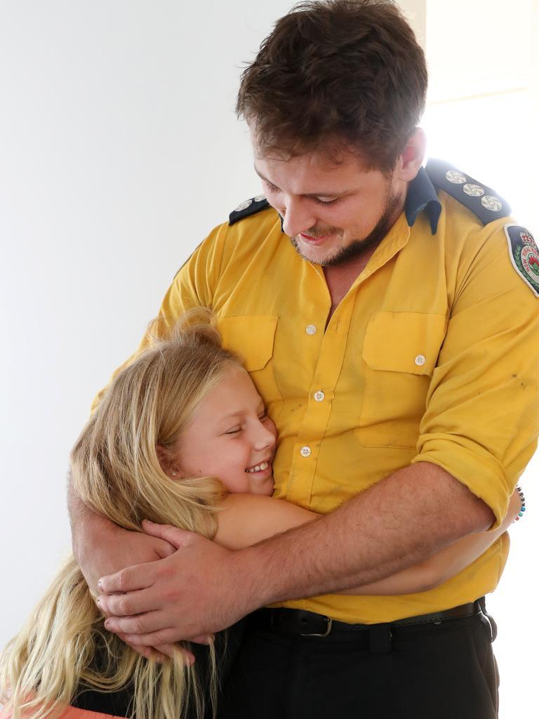 Kesha Pauling, 7, hugs RFS firefighter Nathan Barnden. Picture: Jonathan Ng