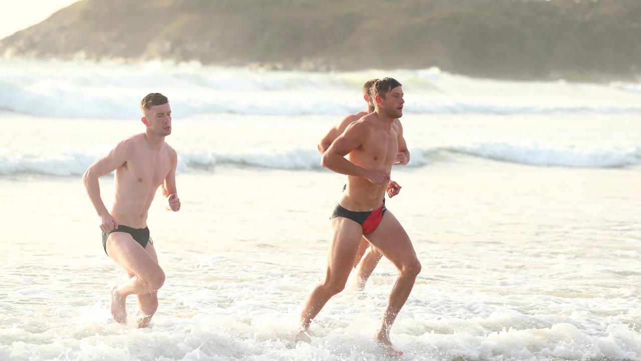 Essendon players return to the beach after a swim.