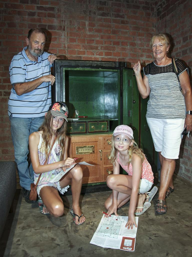 Maddison and Chloe Smith from the Gold Coast look for 'mice' in the Story Bank's old bank vault with grandparents Tony Van Lysdonk and Carol Bradtke from Kilkivan.
