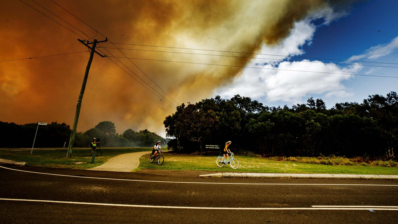 Coolum school kids evacuate on their bikes as a bushfire rages between Coolum and Peregian Beach. Picture: Lachie Millard