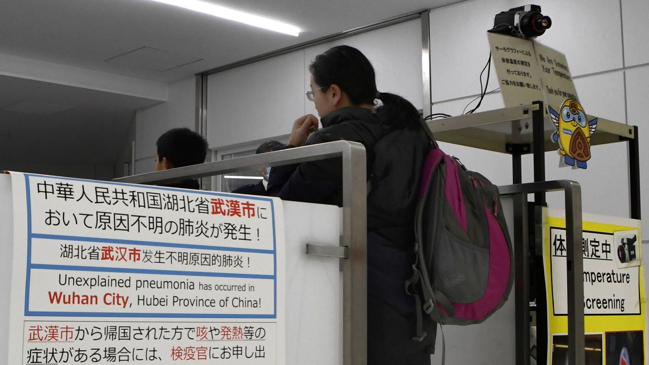 Travellers from Wuhan, in China, where a new strain of coronavirus has killed four people, go through a quarantine station at Narita Airport, near Tokya. Picture: Kyodo News/AP