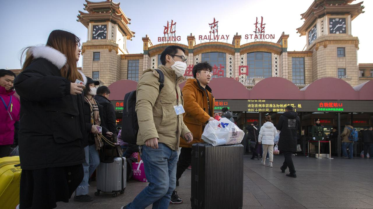 A traveller wears a face mask as he walks outside Beijing Railway Station after a sharp rise in the number of people infected with a new coronavirus, including the first cases in the capital. Picture: Mark Schiefelbein