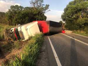 Driver's lucky escape after truck rollover on Pac Hwy