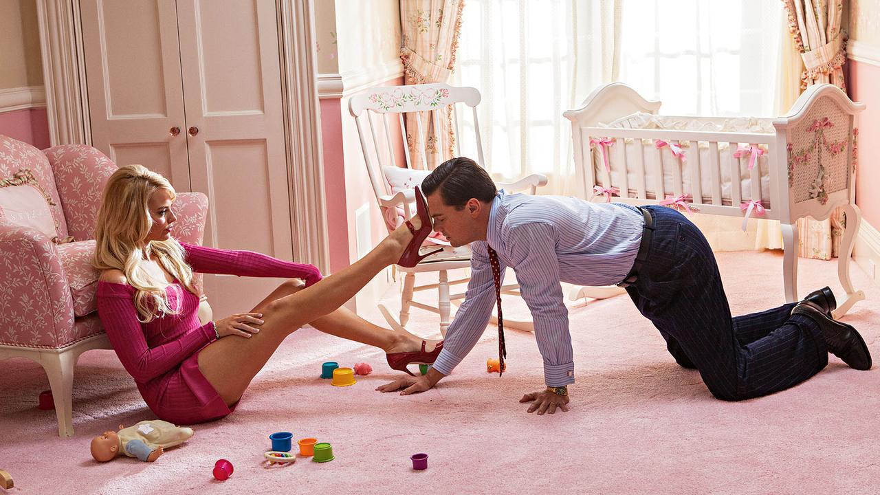 Margot Robbie is Naomi Lapaglia and Leonardo DiCaprio is Jordan Belfort in the film The Wolf of Wall Street.