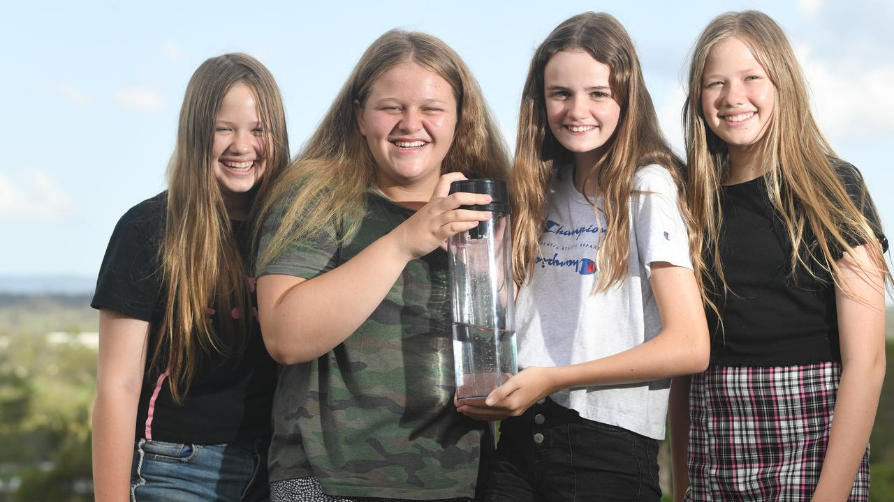 Charlotte McIntosh, Anna Niemand, Ella Shepherd and Addy McIntosh holding the rain gauge with 100mm of rainfall which fell on the Southside during the severe storms last night. Photo: Troy Jegers