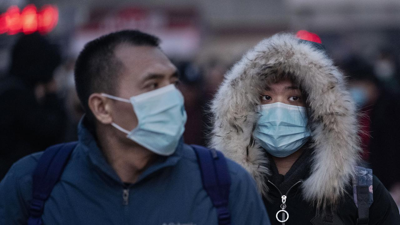 Chinese travellers wear protective masks as they arrive to board trains at Beijing Railway station. Picture: Kevin Frayer/Getty Images