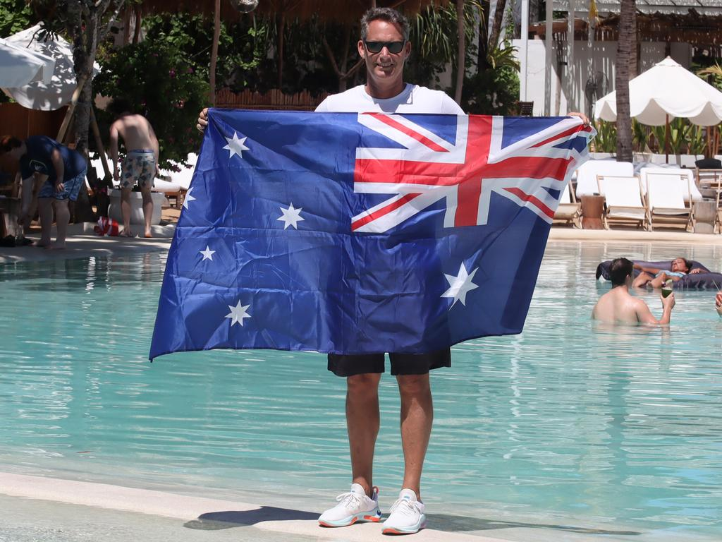 Andrew Stanway holding the Australian flag in the pool of his Mrs Sippy Restaurant in Seminyak, Bali. Picture: Lukman S.Bintoro