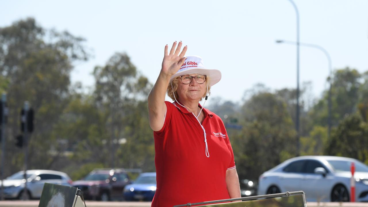 Council candidate Toni Gibbs waves to traffic near the One Mile bridge on Thursday morning.