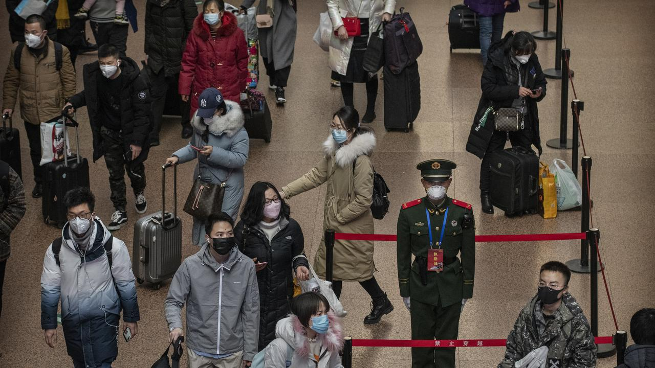 A Chinese police officer wears a protective mask as passengers, arrive to board trains before the annual Spring Festival at a Beijing railway station on January 23, 2020 in Beijing, China. Picture: Kevin Frayer/Getty Images.