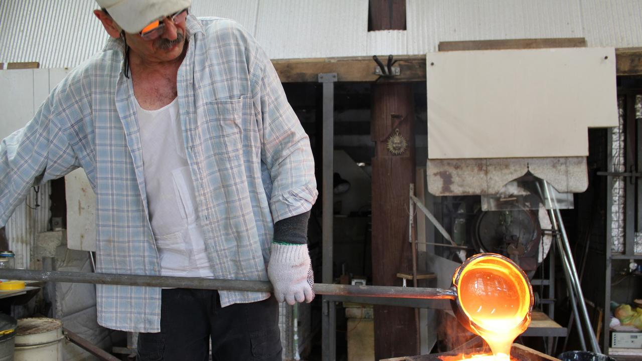 Marc Kalifa pouring molten glass into a sand box.