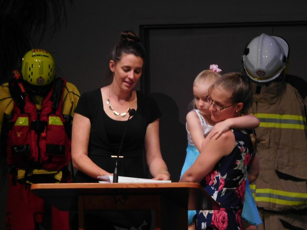 Natasha Salanitri with Jason Caswell's daughter Darci and wife Karen as Natasha read out a story written by Darci about her dad at his funeral at the Seventh Day Adventist Church in Rockhampton.