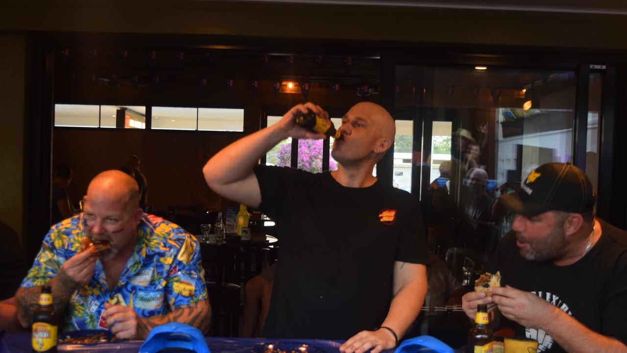 FIRST CHAMP: Toby Curtis (middle) finishes his beer to cap off his victory in the Biloela Hotel's first Pie Eating contest.