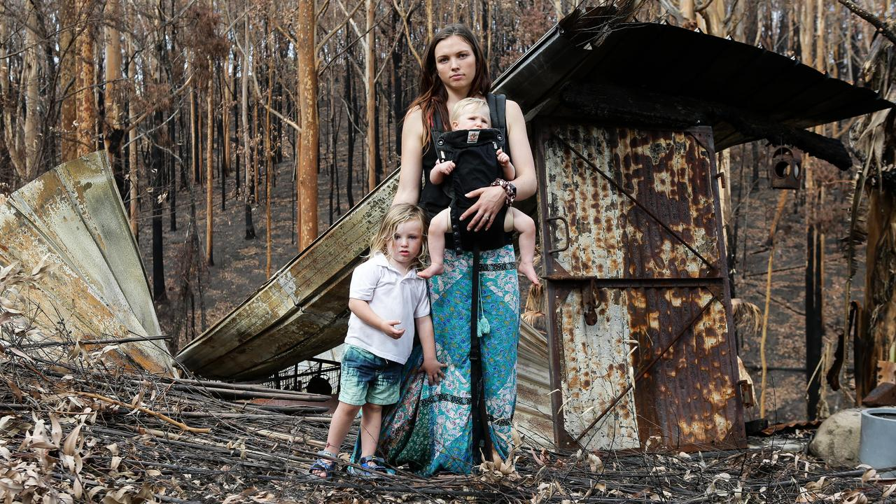 Roxanne Buchanan with her son Jack Hyde, baby daughter Billie and dog Tiddes at her parent's burnt property. Picture: Gaye Gerard