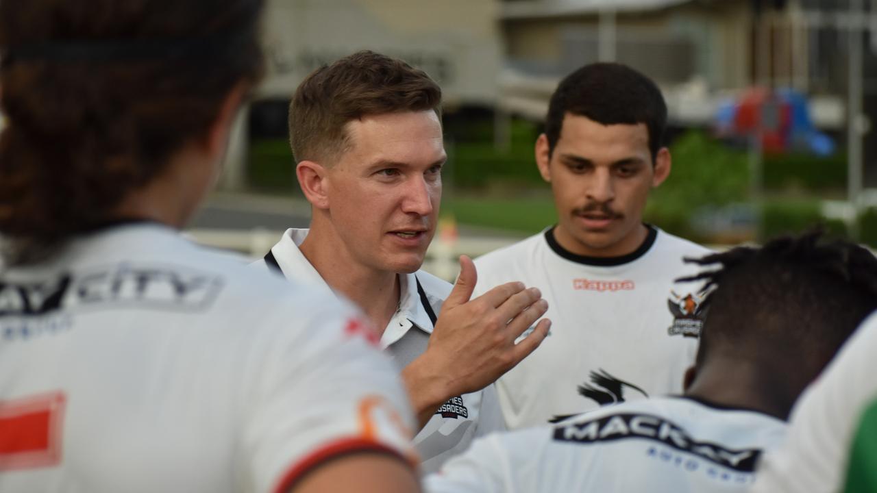 MCU coach Tom Ballantyne gives a halftime talk to his team in a friendly match against the CQ Rep team.