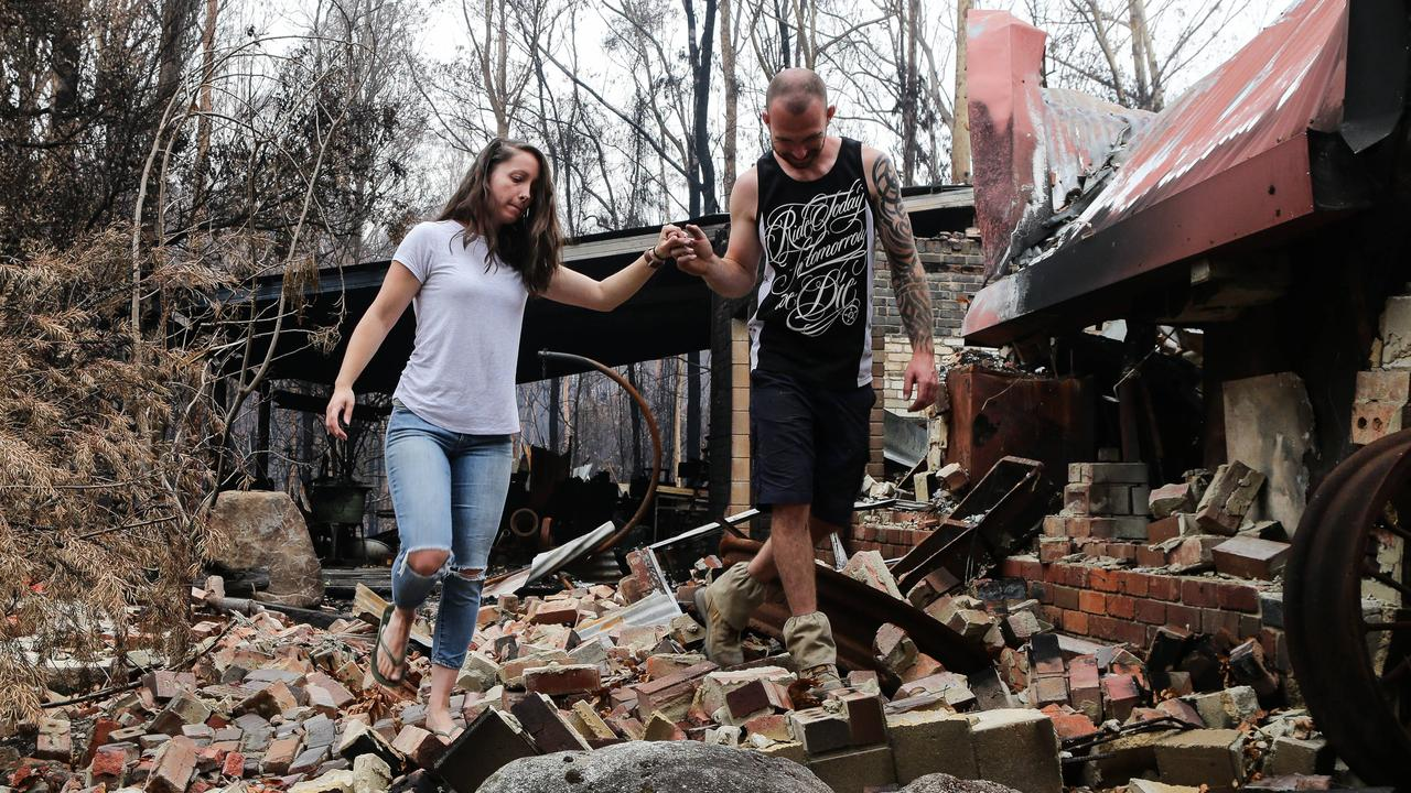 Bo and Stacey Buchanan walk through the wreckage of their home next door to Bo's parents home, which also burnt to the ground. Picture: Gaye Gerard