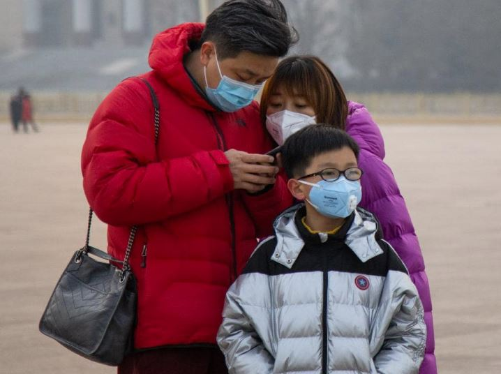 A family wearing masks stands in Tiananmen Square. About 100 Australian school children are thought to be stranded in Wuhan. Picture: Betsy Joles/Getty Images