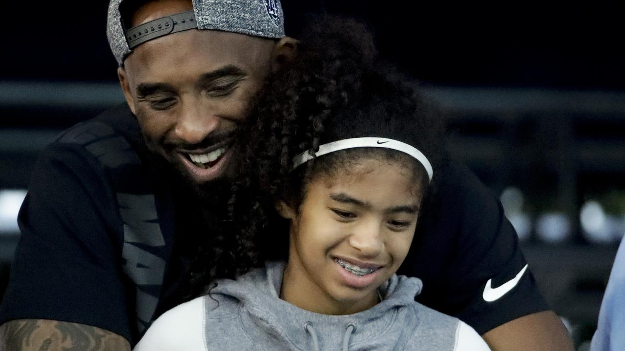 Former Los Angeles Laker Kobe Bryant and his daughter Gianna watch during the US national championships swimming meet in Irvine, California in July 2018. Picture: Chris Carlson/AP