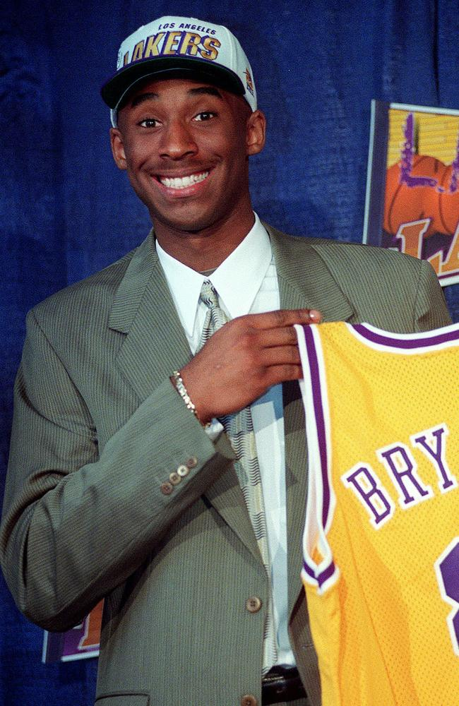 Kobe Bryant, 17, jokes with the media as he holds his Los Angeles Lakers jersey during a news conference at the Great Western Forum in Inglewood, California. Picture: Getty