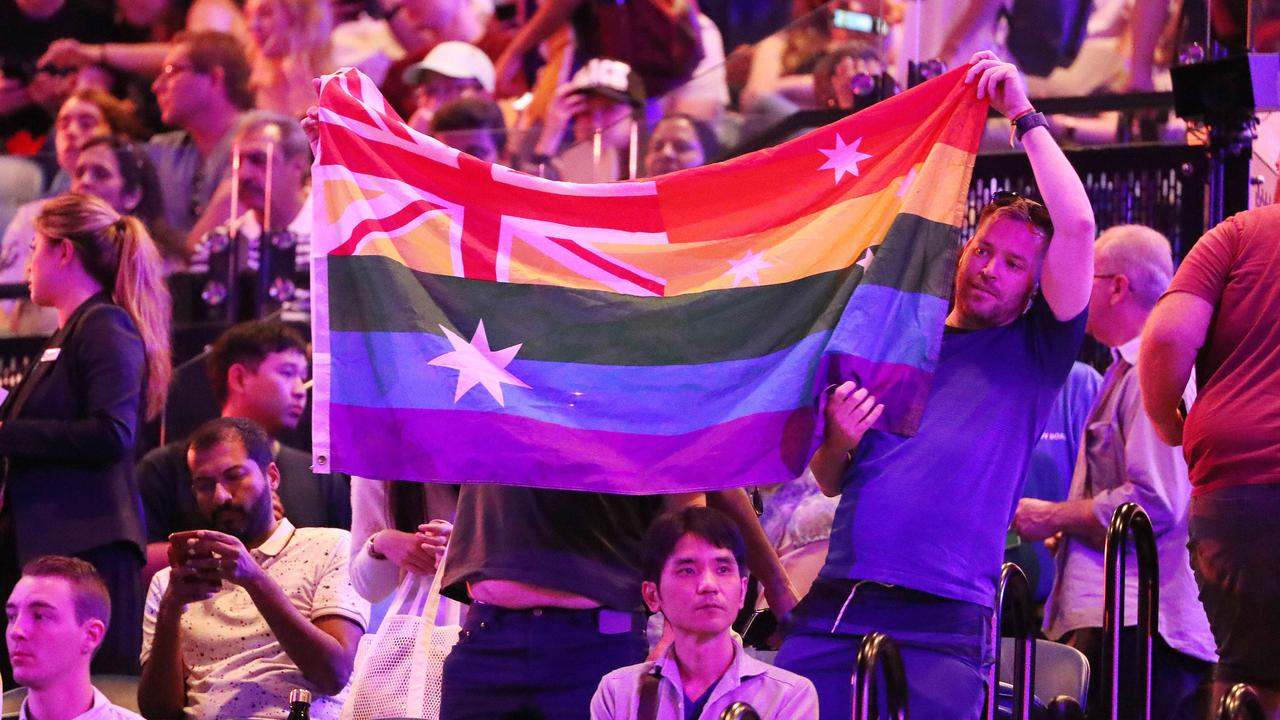 Crowd members hold a rainbow flag during the Margaret Court presentation. Picture: Mark Stewart