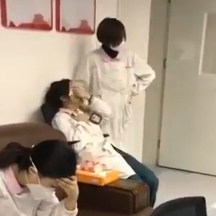 A colleague in a medical mask tries to comfort the woman as she wipes her tears with a tissue. Picture: Supplied