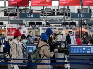 Tourists wear masks at airport check-in