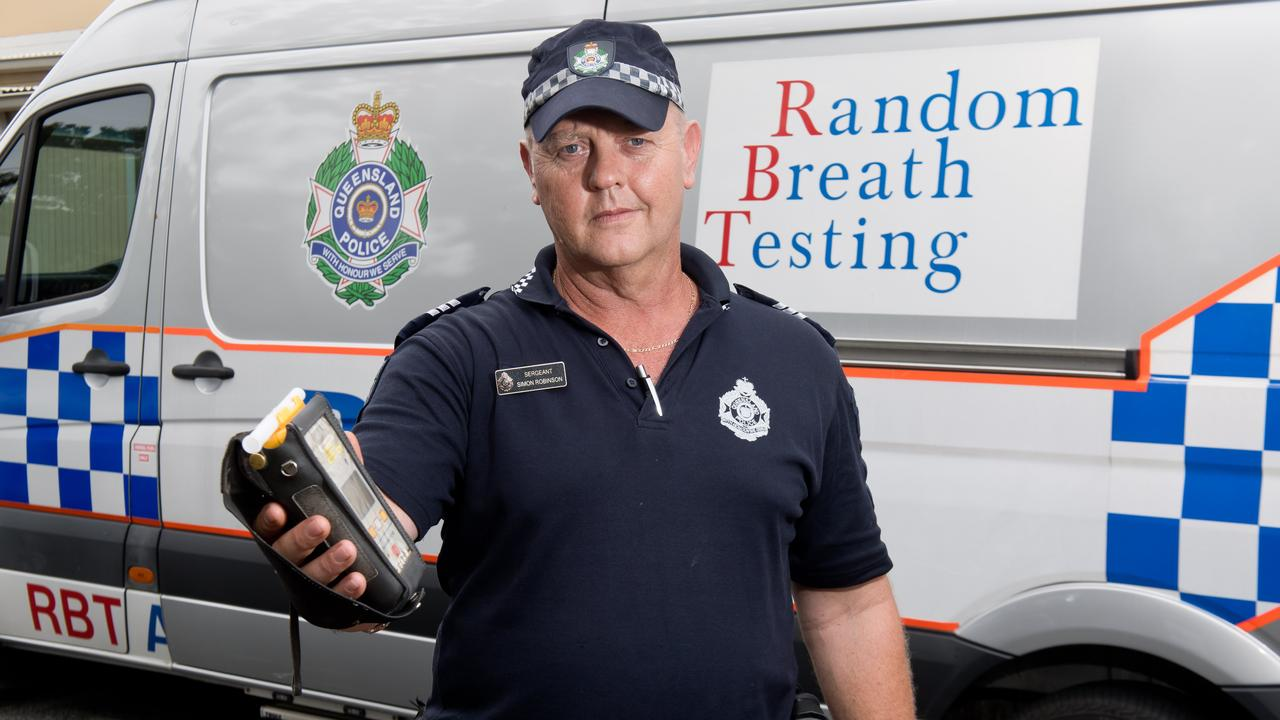 Sergeant Simon Robinson, with a breathalyser, warns drivers to obey the road rules.