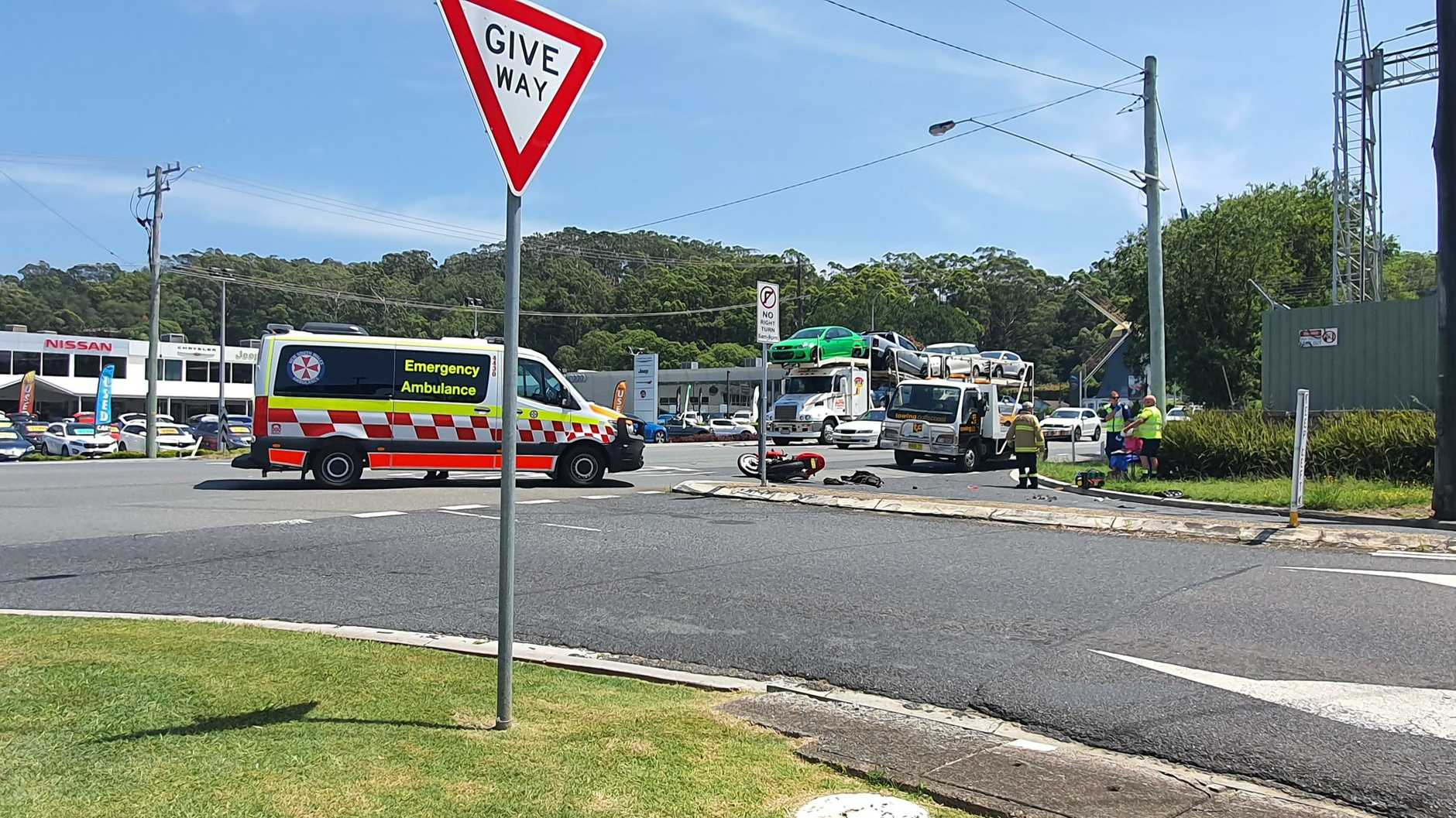Ambulance paramedics are treating an injured motorcyclist on the Pacific Highway at the cross of Thompsons Rd.