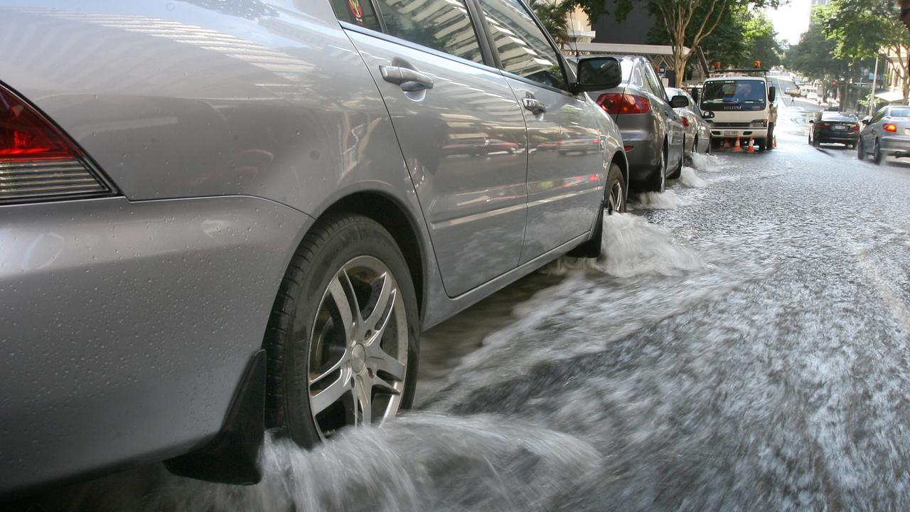 A burst water main on Mary Street in Brisbane city floods the street and flows around parked cars