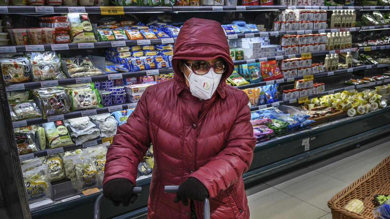 A Chinese woman wears a protective mask and sunglasses as she shops for groceries at a supermarket in Beijing. Picture: Getty Images/Kevin Frayer