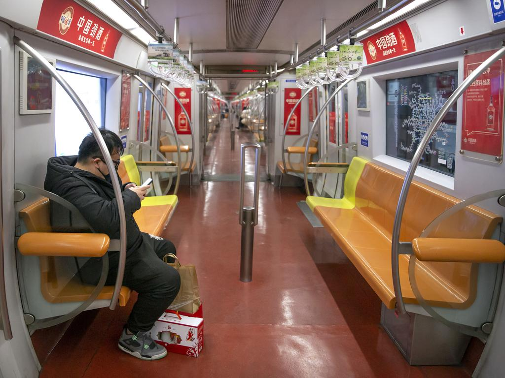A man in a face mask rides an empty subway in Beijing. Picture: AP Photo/Mark Schiefelbein.