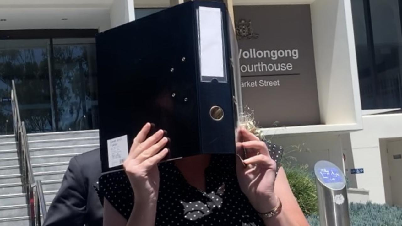 Hingeley again on November 6, she'd change into a different top since her arrival and used a folder to hide her face. Picture: Madeline Crittenden.