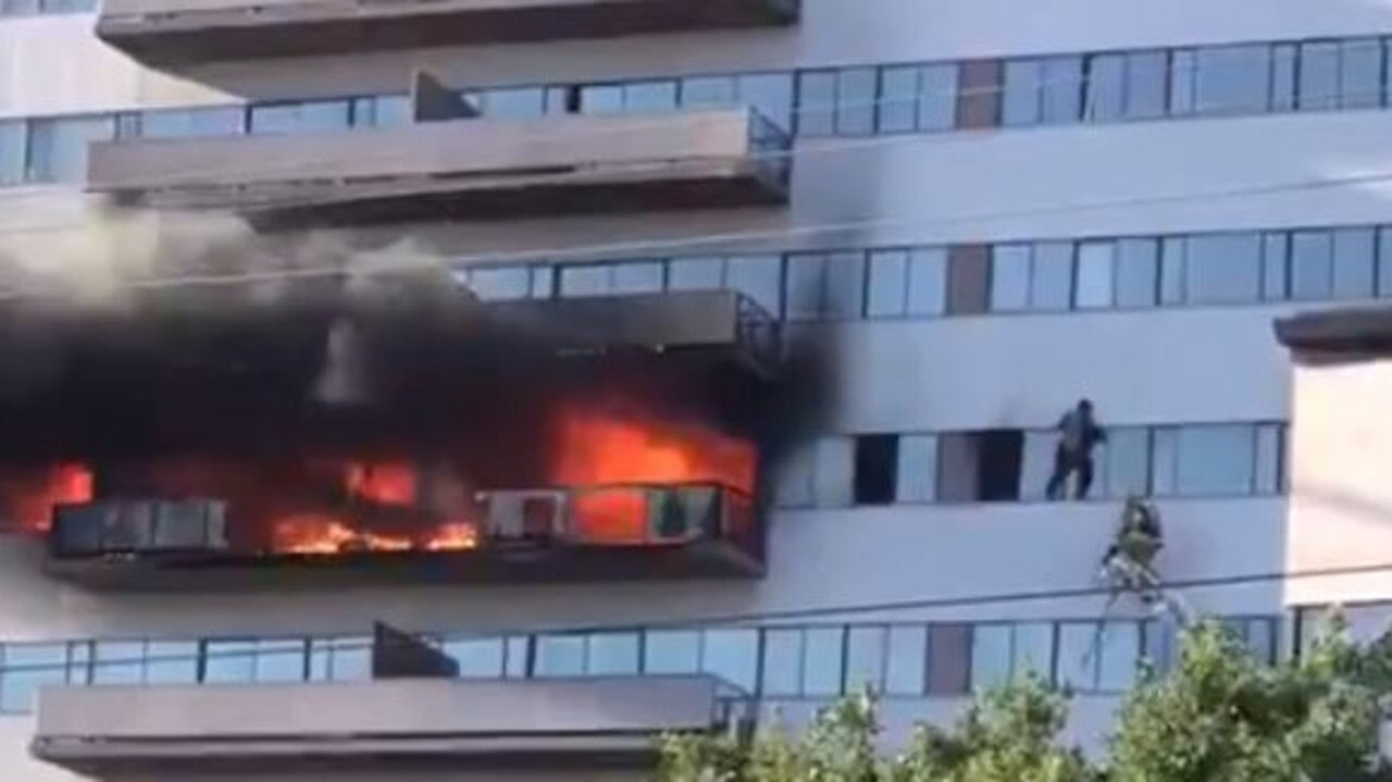 A man climbs outside to escape a fire in a high-rise building in Los Angeles. Picture: Twitter/@HereIsShir