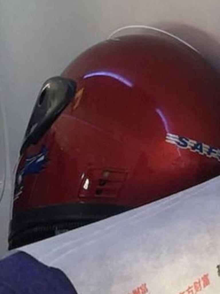 A passenger wears a bike helmet on a flight from Shanghai. Picture: 7 News