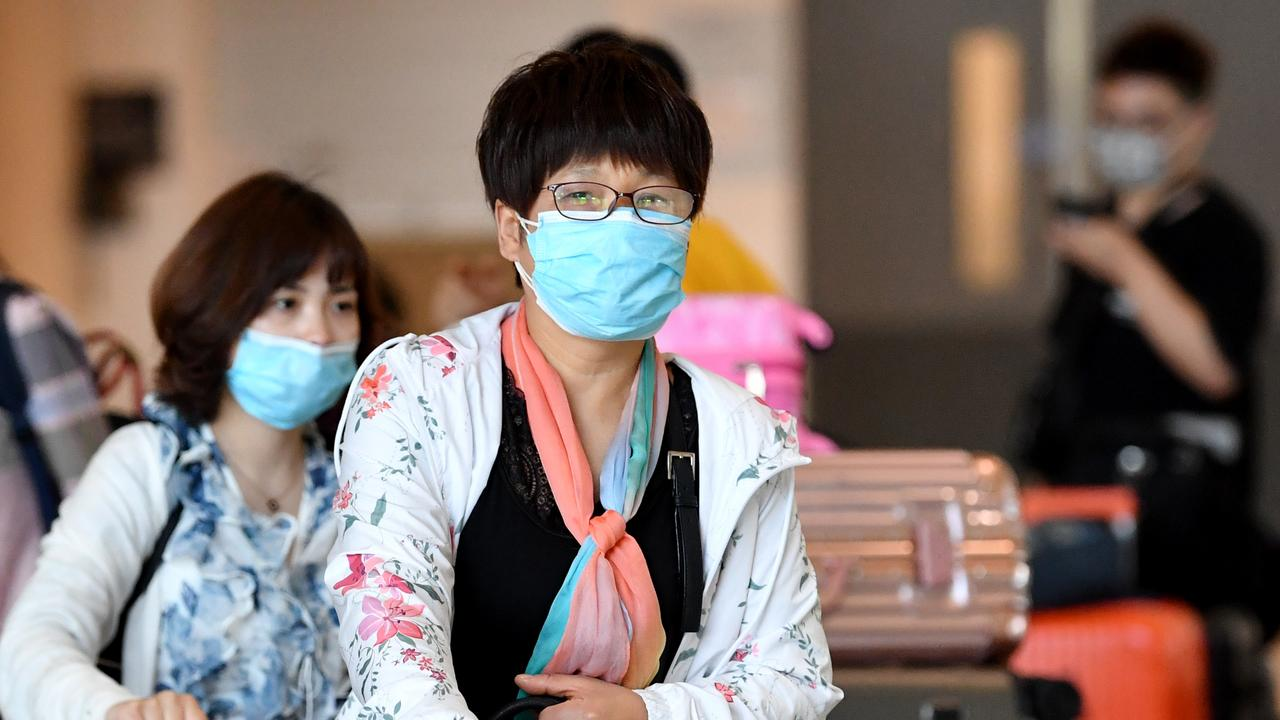 Travellers at Brisbane International Airport wearing masks as a precaution this week. Picture: AAP Image/Darren England
