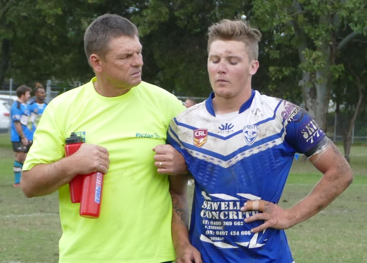 Grafton Ghosts centre Cooper Woods helped from the field after he was concussed in a clash with an opposition player.