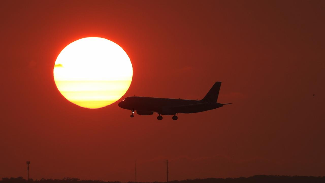 A Smokey sunrise over Sydney Airport ahead of forecasted hot days .picture John Grainger