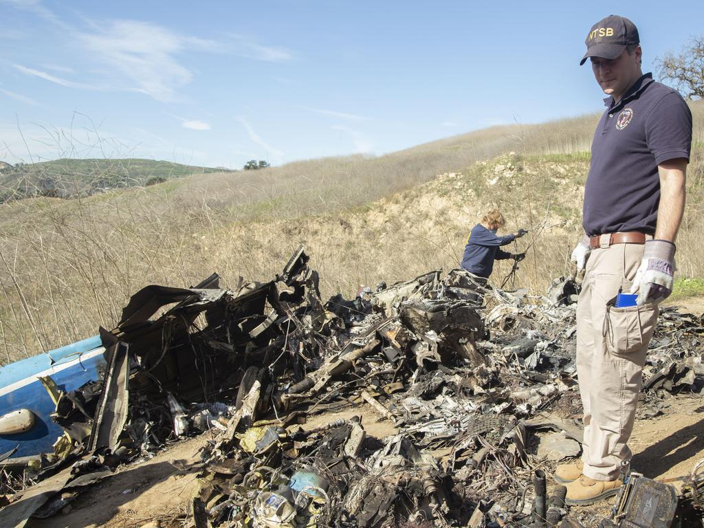 The National Transportation Safety Board, NTSB investigators Adam Huray, right, and Carol Hogan examine wreckage as part of the investigation of a helicopter crash near Calabasas. Picture: AP