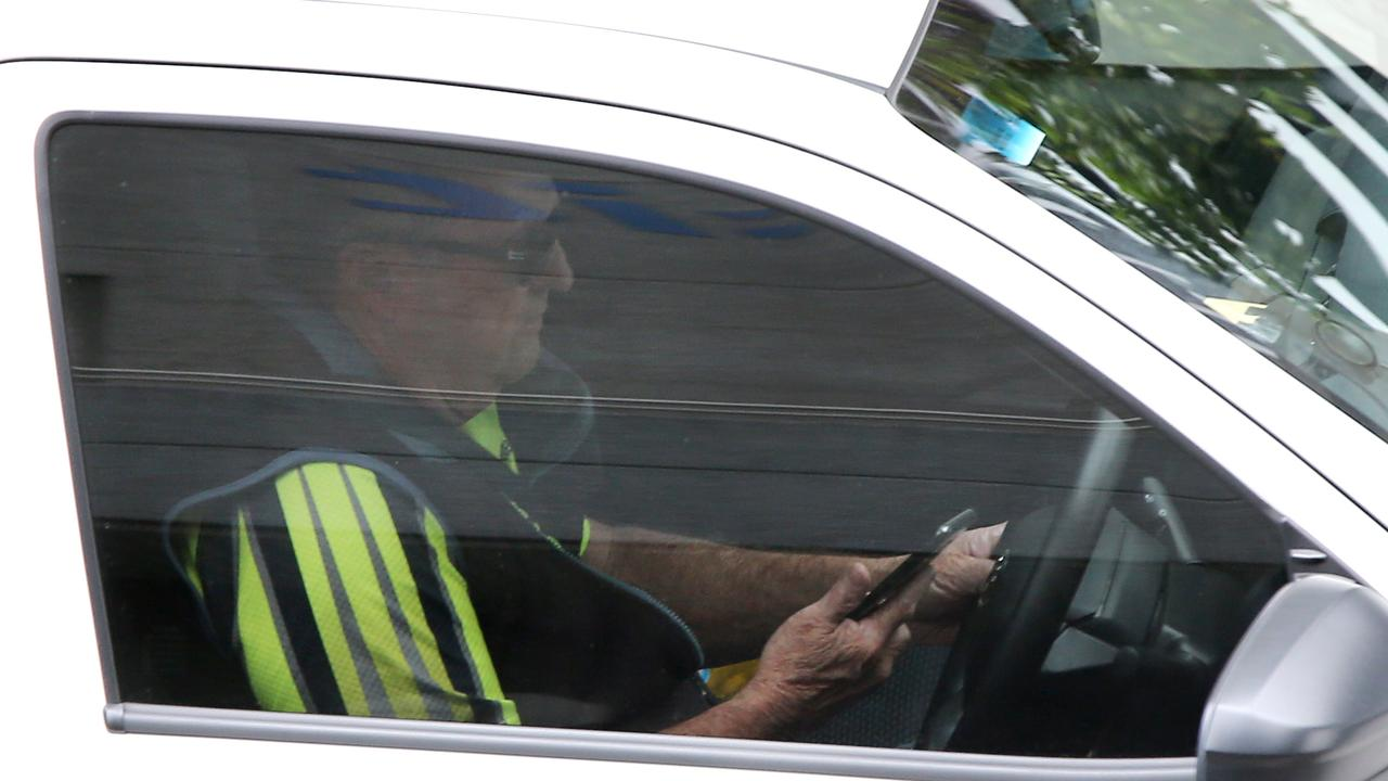 "The Queensland Road Rules say a driver ""must not use a mobile phone that the driver is holding … while the vehicle is moving, or is stationary but not parked"". Picture AAP/ David Clark"