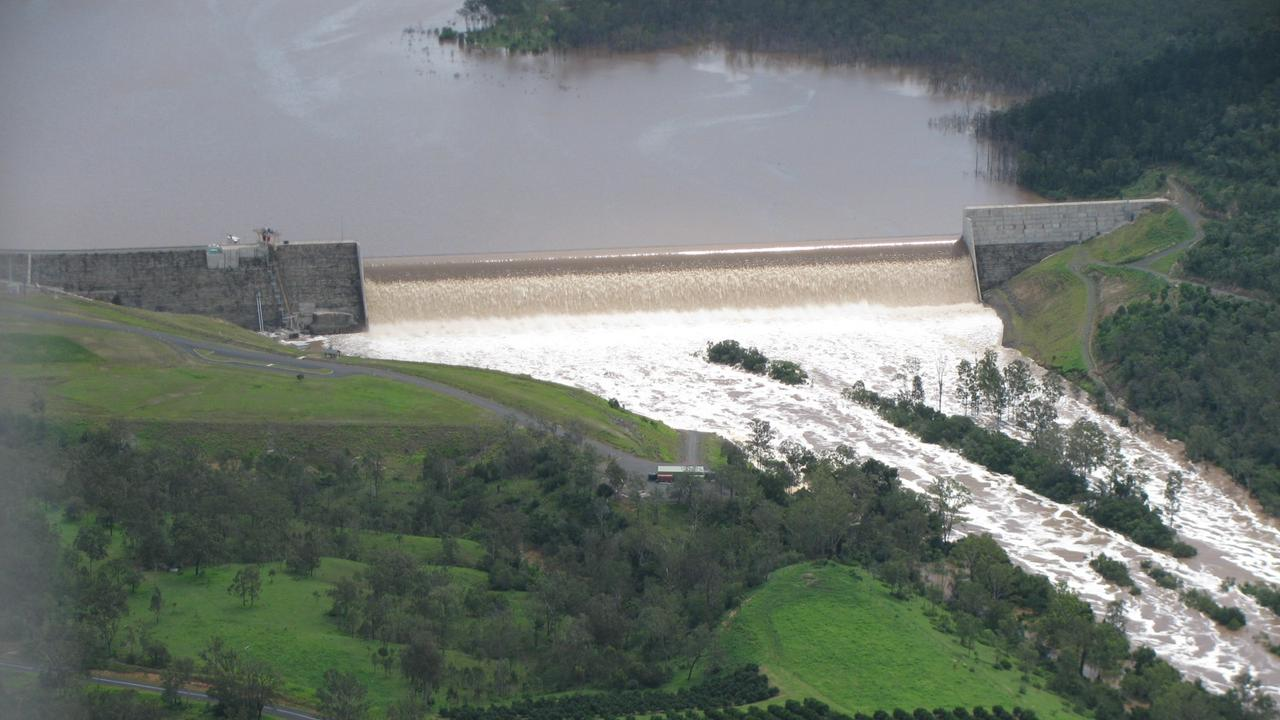 GOING DOWN: Paradise Dam overflowing. Following damage caused by the 2013 flood, the State Government has decided to lower the dam's spillway by 5m.