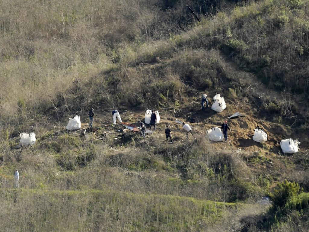 Investigators work at the scene of the helicopter crash.