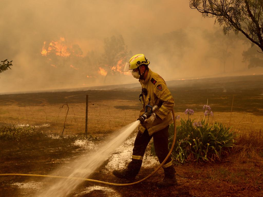 Fire and Rescue NSW firefighters put out spot fires in the Bega Valley, near Wyndham. Picture: Toby Zerna