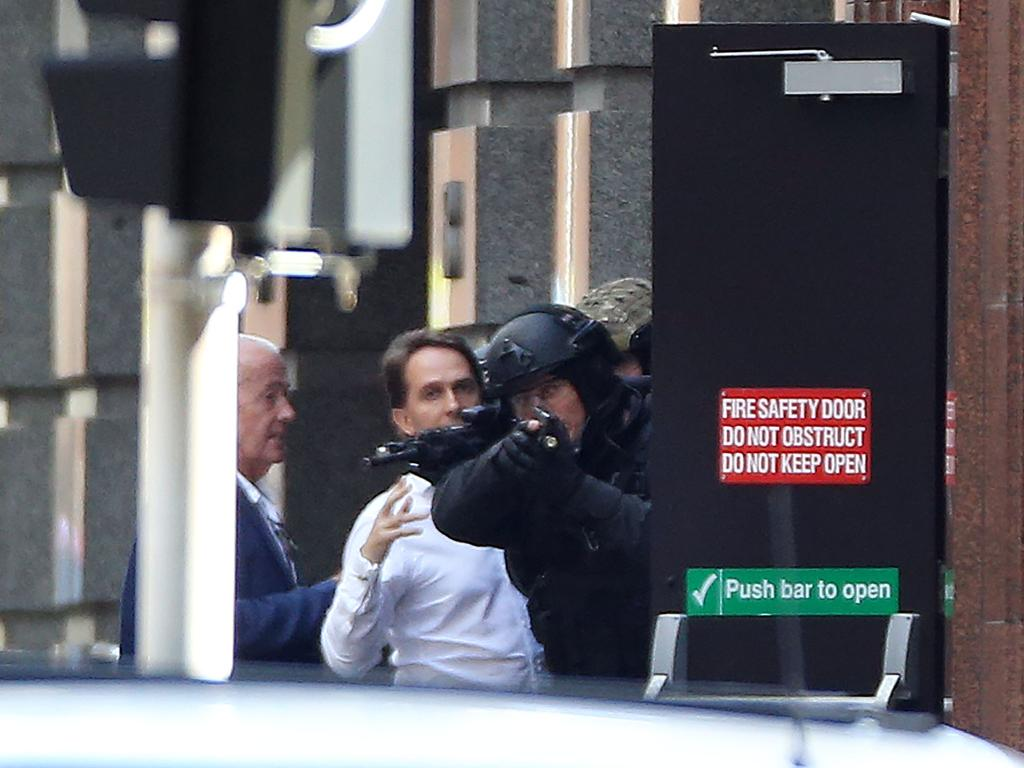 Hostages John O'Brien and Stefan Balafoutis run to the safety of police after escaping the Cafe. Picture: Craig Greenhill