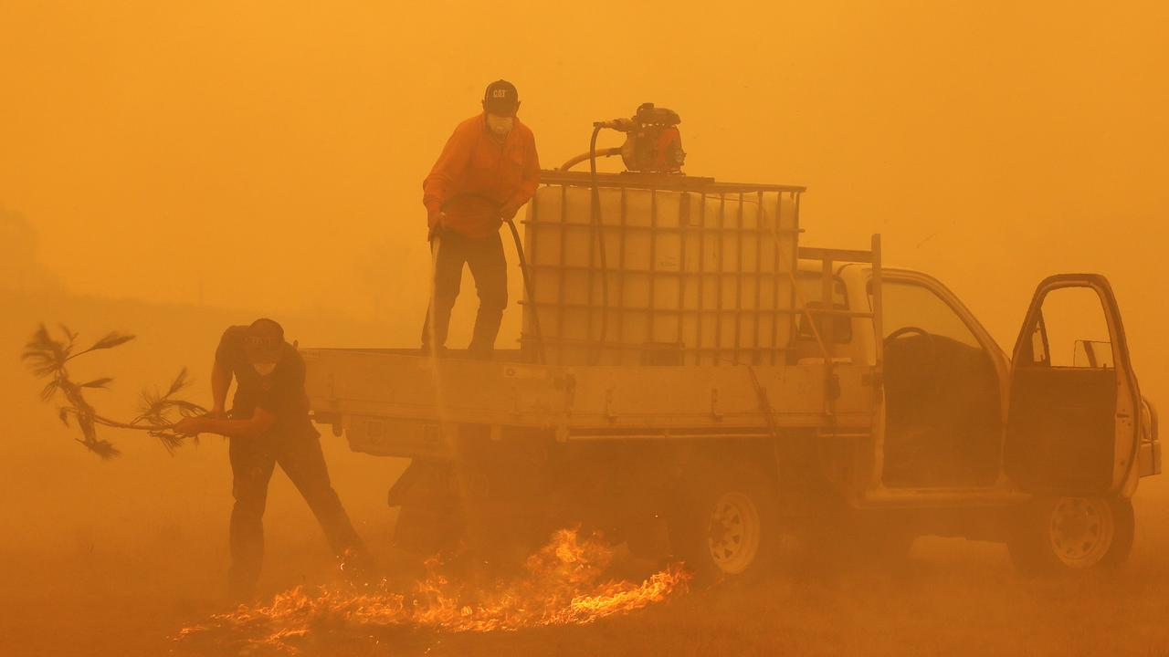 Sheldon Evans (L) and Chris Veness put out spot fires in the Bega Valley near Wyndham. Picture: Toby Zerna