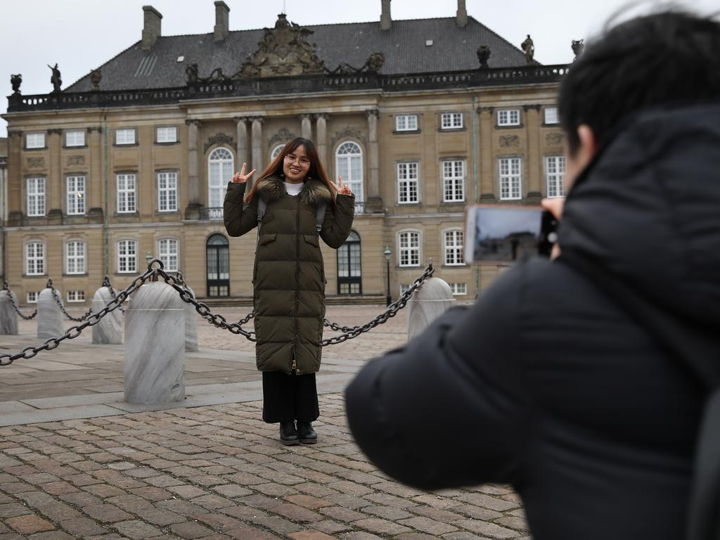 Tourists visit Amalienborg palace, home of the Danish royal family, in Copenhagen. Picture Ella Pellegrini