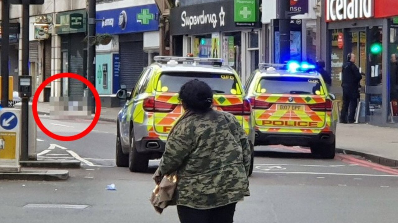 The shot man pictured lying outside a Boots while officers stand in the Iceland entrance. Picture: Supplied