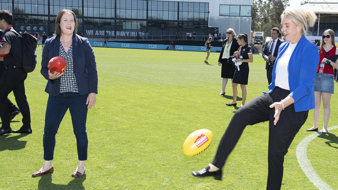 Kelly O'Dwyer and the then Minister for Sport, Bridget McKenzie have a kick on the ground after the announcement of a $15 million funding boost to develop Ikon Park, Melbourne, in February last year. (AAP Image/Ellen Smith)
