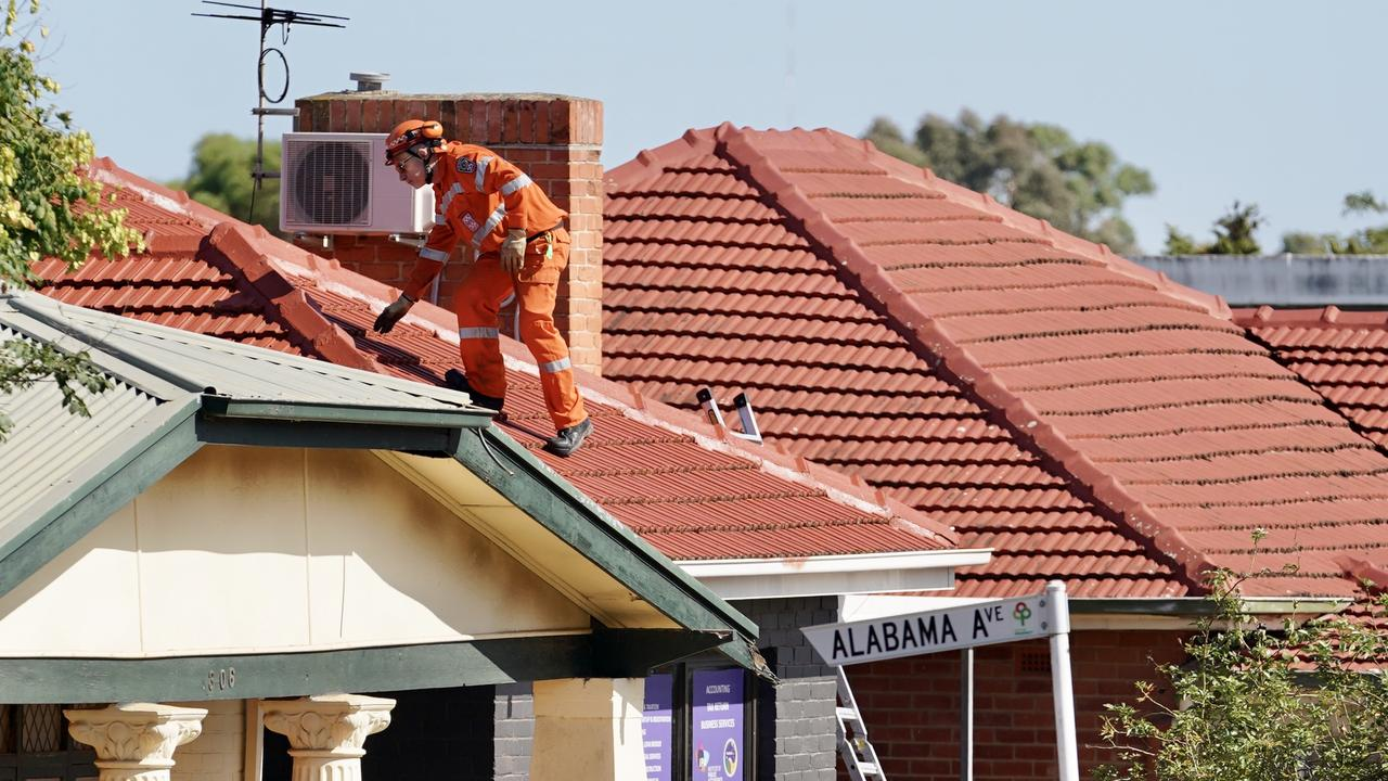 An SES worker searches a rooftop for evidence. Picture: AAP / Mike Burton